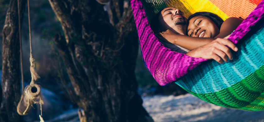 Mixed couple sleeping in hammock on a sandy beach by the sea